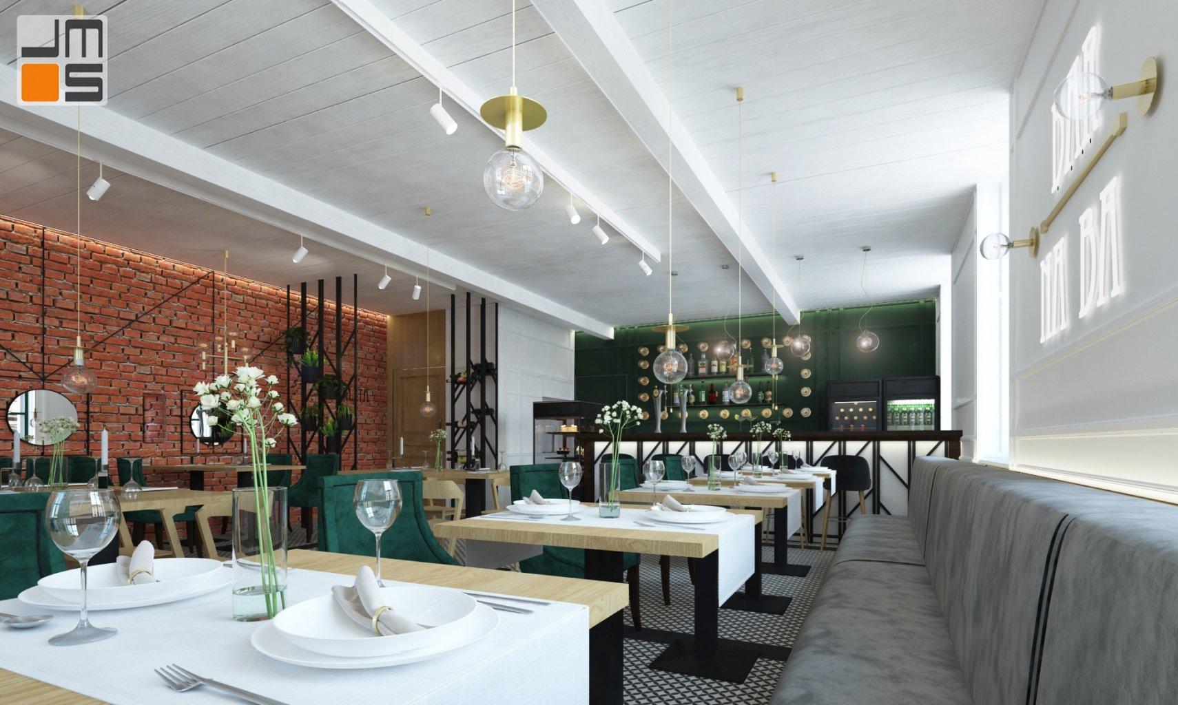 w projekcie wnętrz baru restauracji w Krakowie cegła pięknie łączy się z zielonymi i złotymi dodatkami w białych jasnych wnętrzach