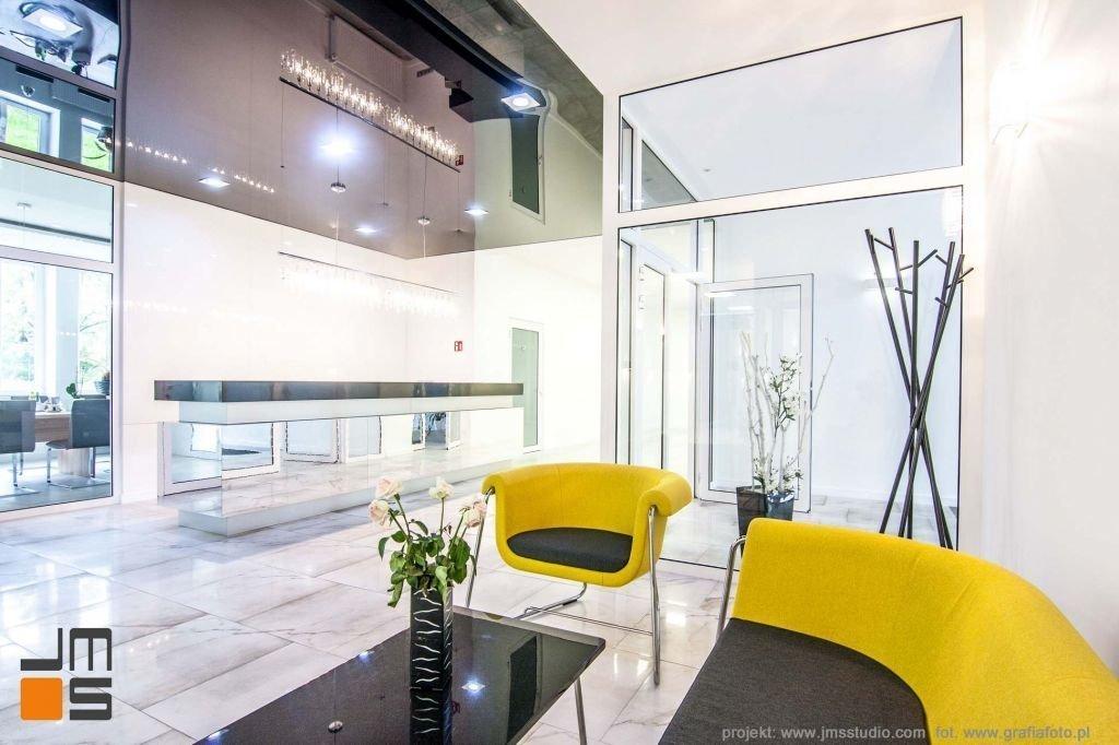 Wnetrze w kolorach spokojnej szarości bieli i czerni z zółtym akcentem kolorystycznym w foyer biura