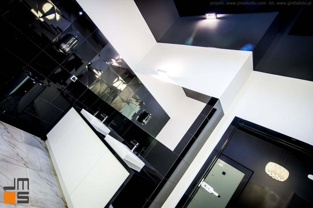 Ciemne odbijające lustrzane powierzchnie w aranżacji wnętrz nowoczesnej łazienki w biurach