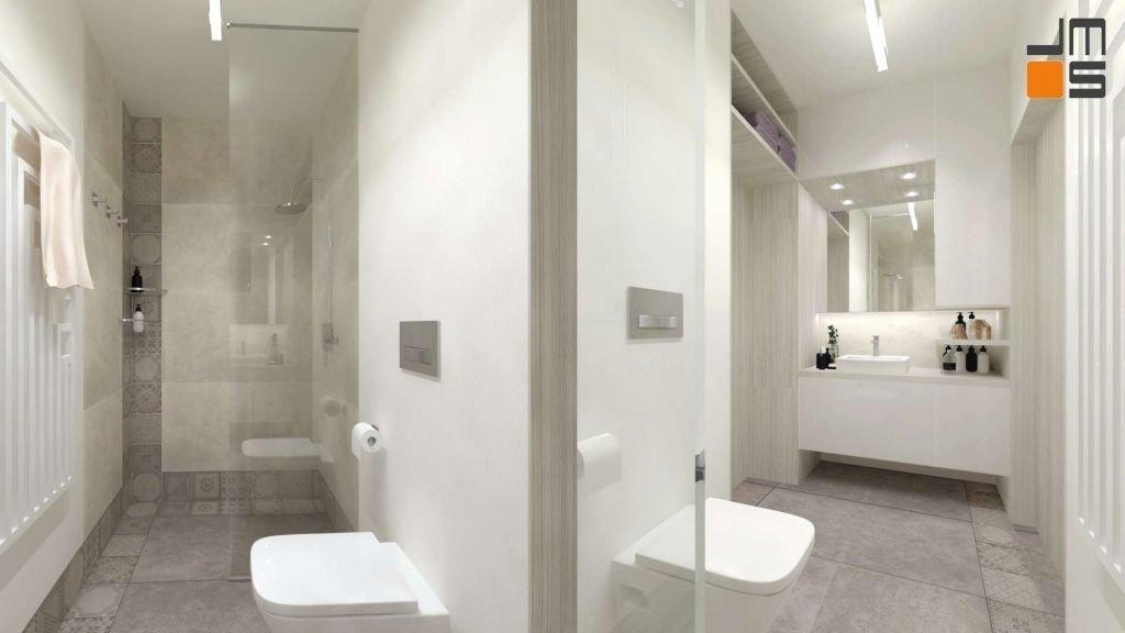 Umywalka na blacie szafki wiszącej jest w jasnej kolorystyce dopasowanej do beżowych płytek zastosowanych w łazience.