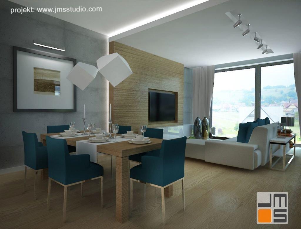 Projekt wnętrz strefy dziennej z jadalnią i salonem. Nowoczesny pomysł na projekt wnętrza z betonem i drewnem na ścianie oraz kolorem turkusowym