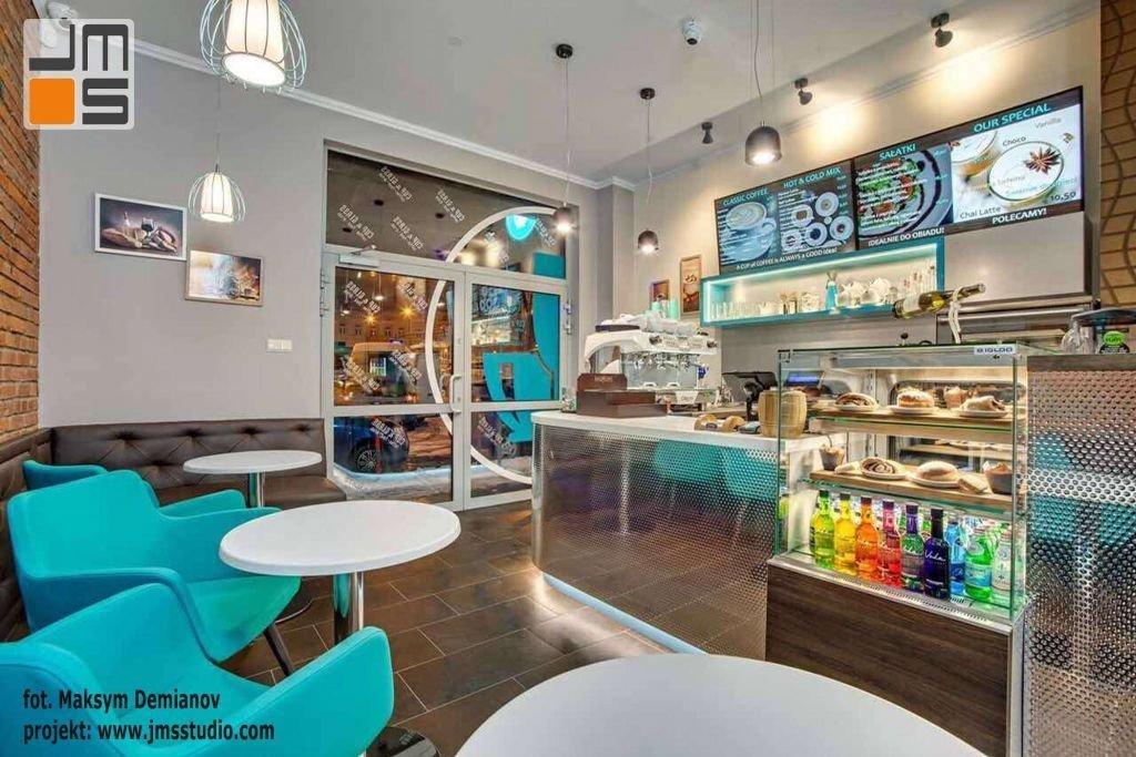 W kawiarni zaprojektowano miejsca siedzące przy stolikach na nowoczesnych turkusowych fotelach