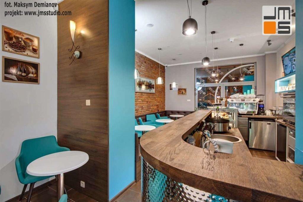 Drewniana lada baru w projekcie wnętrz kawiarni jest wykonana z tego samego drewna co okładzina ściany