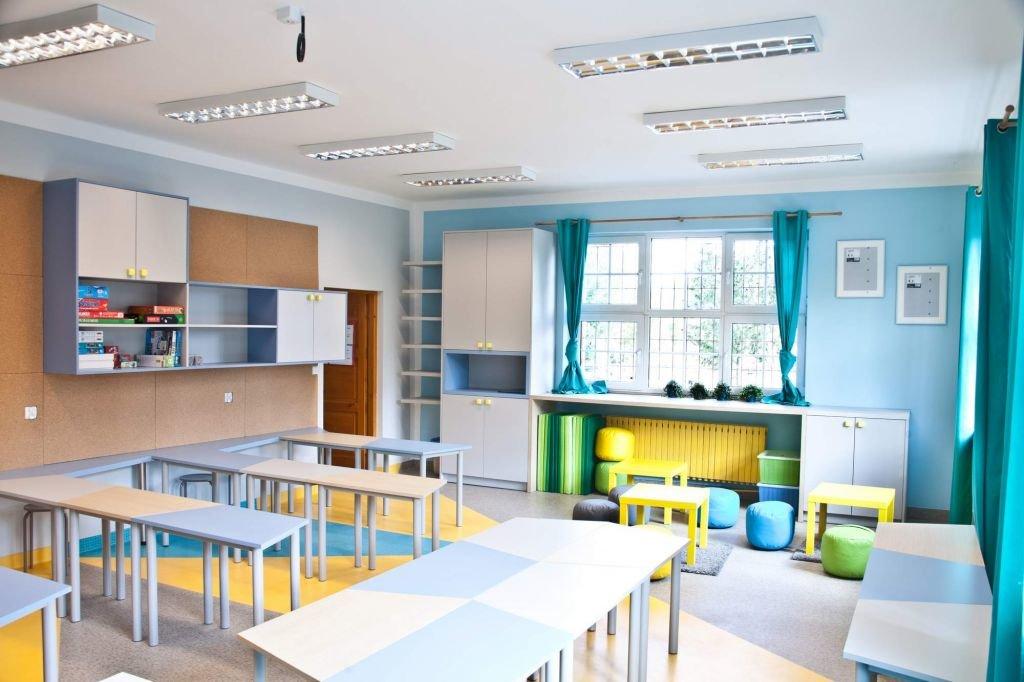 W projekcie wnętrz klasy - świetlicy w szkole nie zabrakło pomysłu na ciekawe ławki, podłogę z wykładziny obiektowej czy drobne dodatki tworzące miły klimat z turkusowymi akcentami we wnętrzu