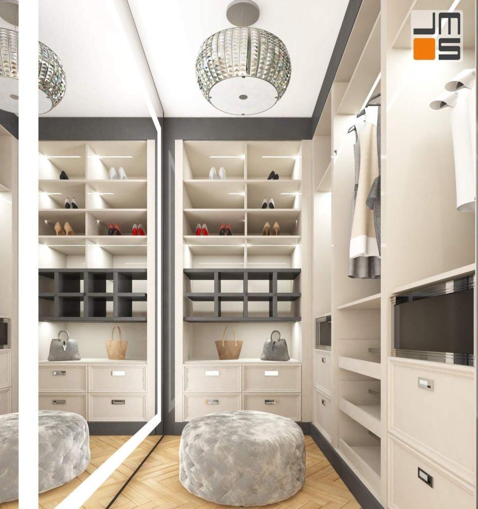 w małej garderobie w apartamencie znalazło sie miejsce na duże lustro i wygodną szarą pufę