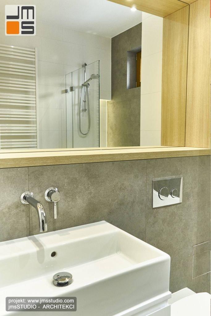 Drewniana rama okalająca duże lustro bardzo dobrze pasuje i komponuje się z szarą płytką gresową ocieplając wnętrze łazienki i podnosząc jego standard.
