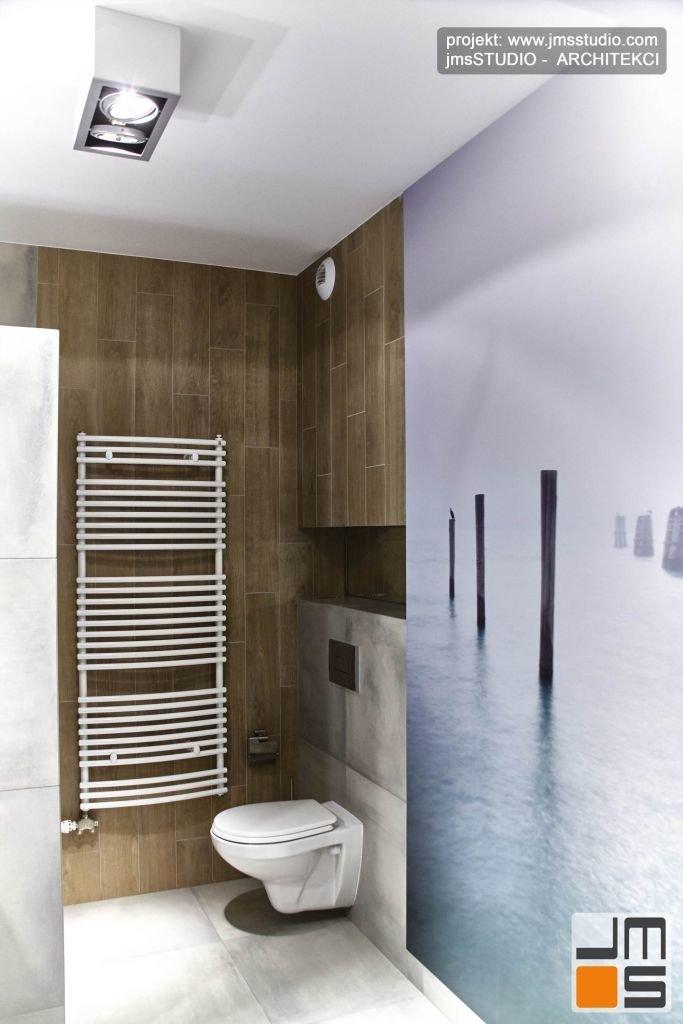 Projekt łazienki z dużą grafiką w kolorach turkusu z motywem morskim - falochron wydrukowano na tapecie firmy VESTIGE z Krakowa