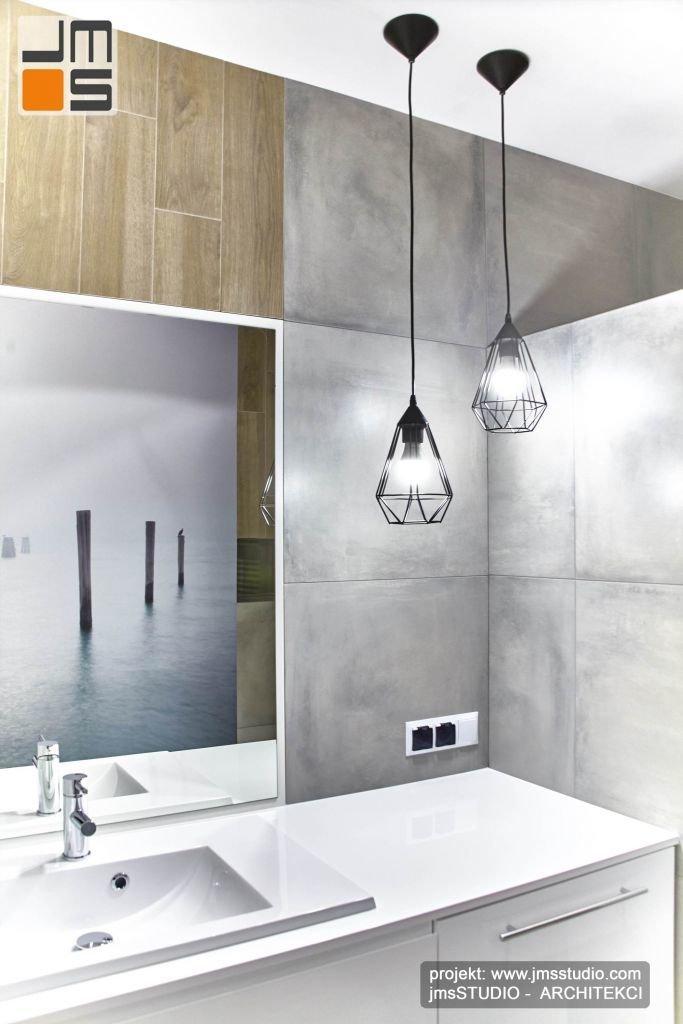 Jasne lakierowane meble łazienkowe w połączeniu z szarą płytką gresową dużym lustrem i nowoczesnymi czarnymi lampami we wnętrzu łazienki