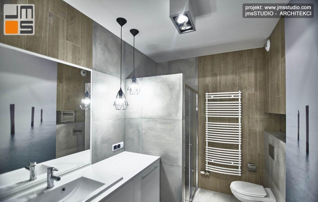 Płytka drewnopodobna stanowi element ocieplający wnetrze łazienki w szarych kolorach