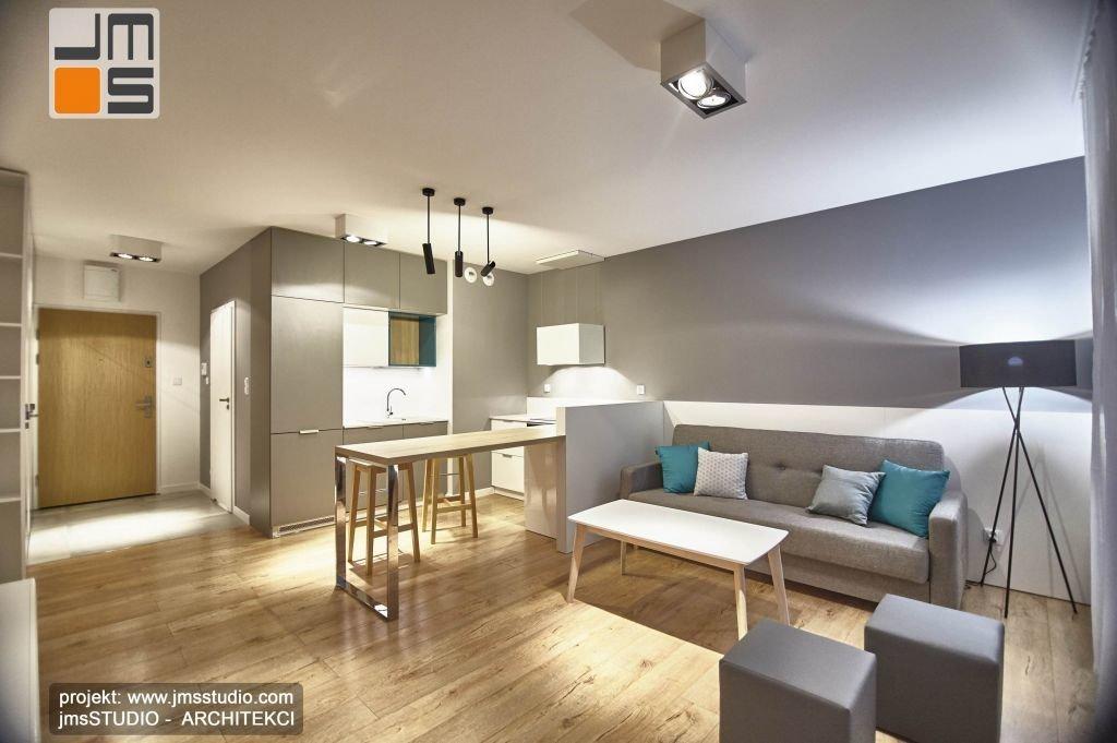 Jasna jesionowa podłoga w kuchni salonie i przestrzeni dziennej mieszkania komponuje się z szarościami ścian i umeblowania mieszkania pod wynajem