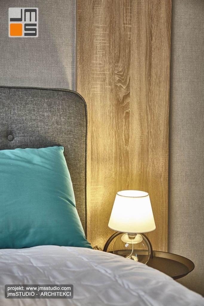 Połączenie trzech różnych materiałów drewno tapeta i ktanina tapicerki w nowoczesnym wnętrzu sypialni.