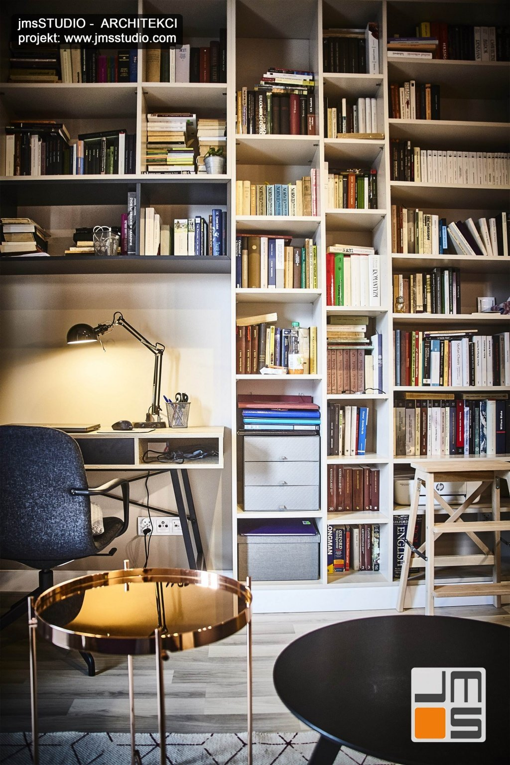 Duży regał na książki w wkomponowanym miejscem do pracy w projekcie wnętrz w stylu soft loft w Krakowie to pomysł na aranżacje designerskiej ściany