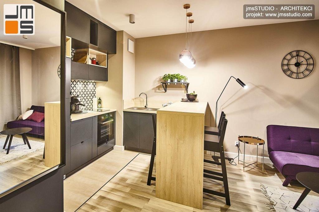Wysoki blat wyspy kuchennej w projekcie wnętrz eleganckiego mieszkania w stylu Soft Loft oddziela elegancką kuchnię od designerskiego salonu w Krakowie