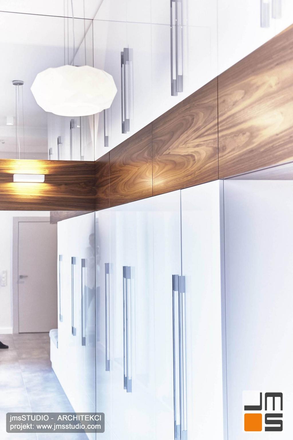 2018 06 w dużym lustrze postaciowym sięgającym sufitu odbijają się meble garderoby przez co ta wydaje się optycznie większa to dobry pomysł projektanta wnętrz Poznań