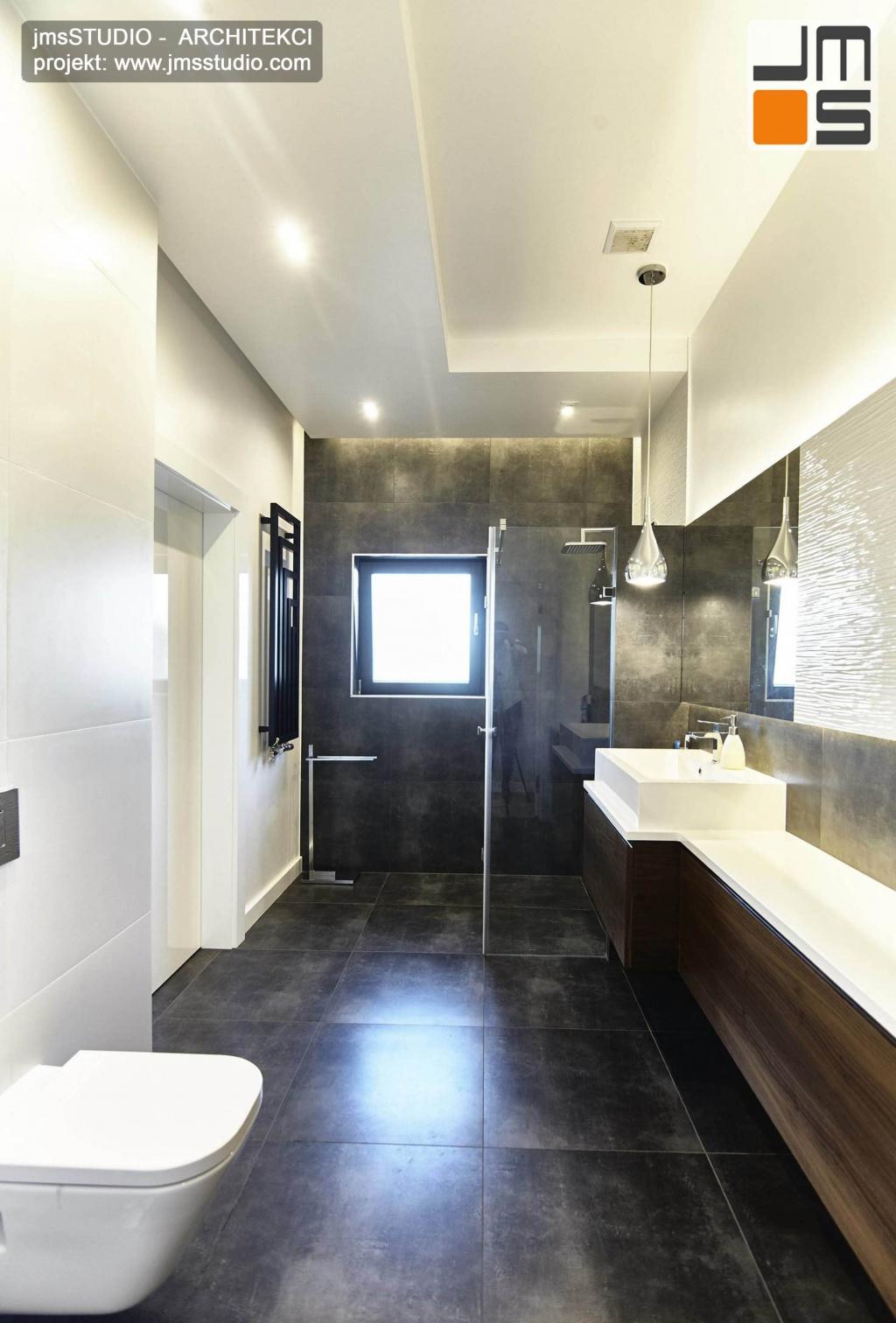 2018 06 w małej  łazience o dziwnym kształcie projekt wnętrz wprowadził sufit podwieszany z ciekawym oświetleniem oraz meble z drewna orzech i ciemne płytki