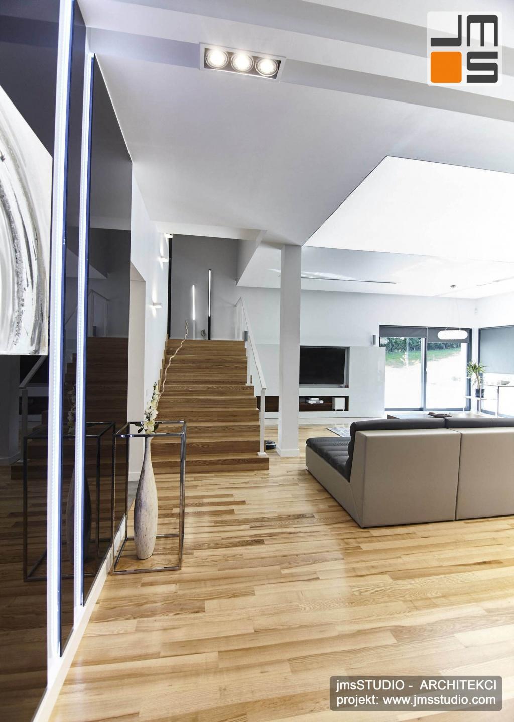 2018 06 z holu otwiera się widok na pięknie zaprojektowane wnętrza salonu oraz duże rozłożyste eleganckie schody na piętro w domu pod Poznaniem