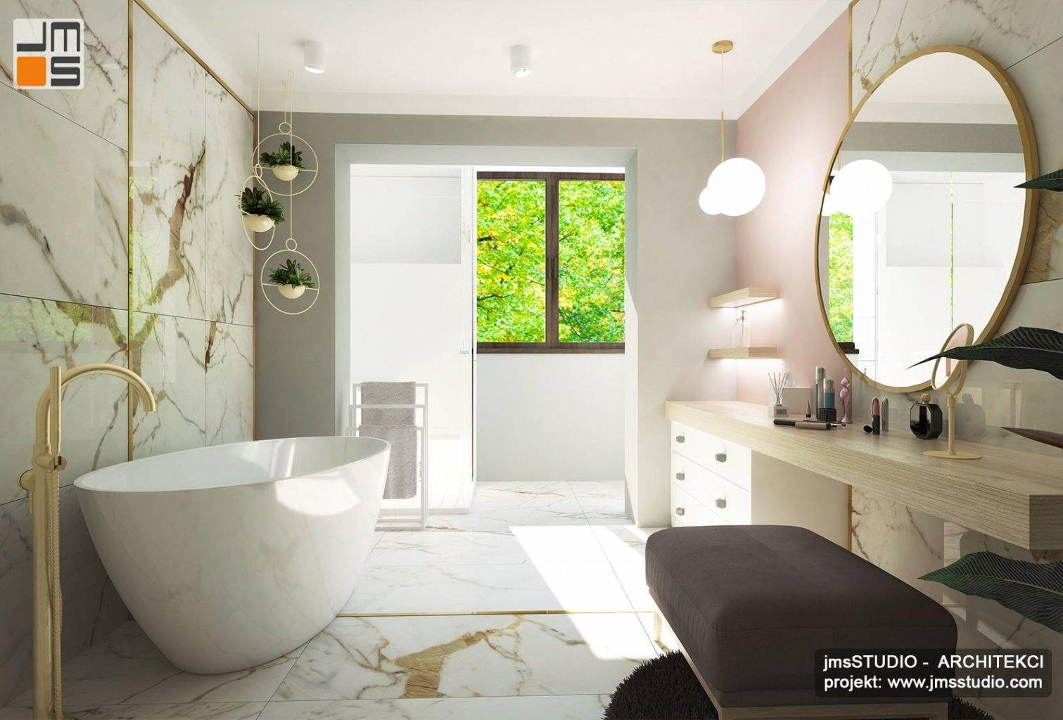 Duże lustro okrągłe wanna wolno stojąca i płytki gresowe marmur to pomysł na wnętrze łazienki Katowice