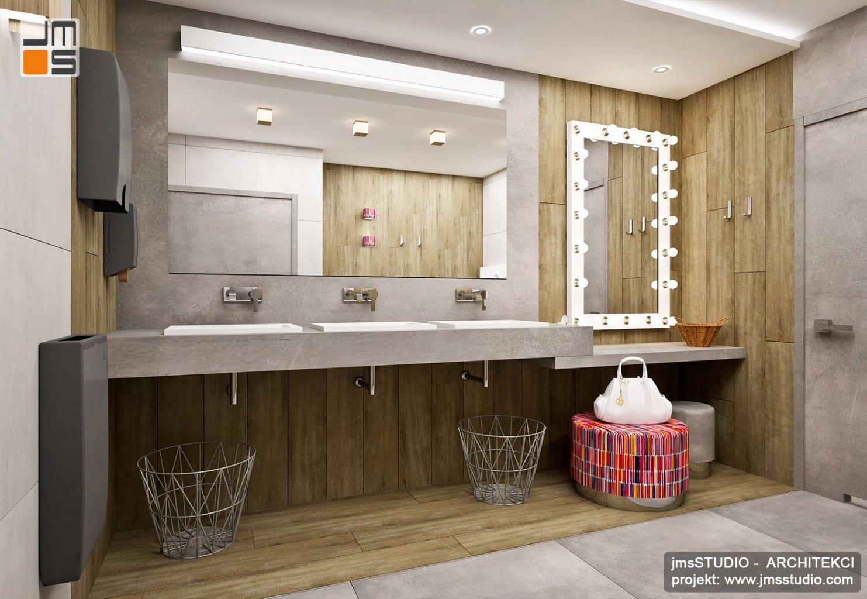 Bardzo ciekawy pomysł na wnętrze z lustrem filmowym drewnem i designerskimi dodatkami w projekcie łazienki w restauracji
