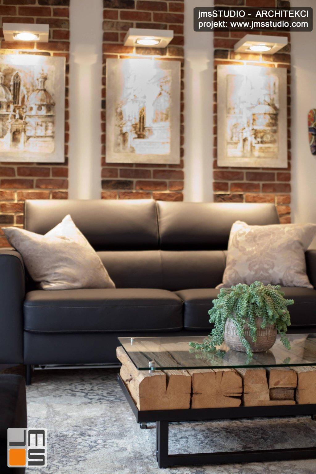 Szara rozkładana sofa i cegła na ścianie salonu to projekt wnętrz małego mieszkania na  Browar Lubicz w Krakowie