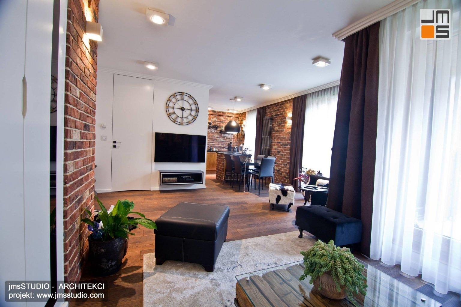 Elegancka strefa dzienna mieszkania w Krakowie - projekt wnętrz klasycznych z cegłą na ścianach