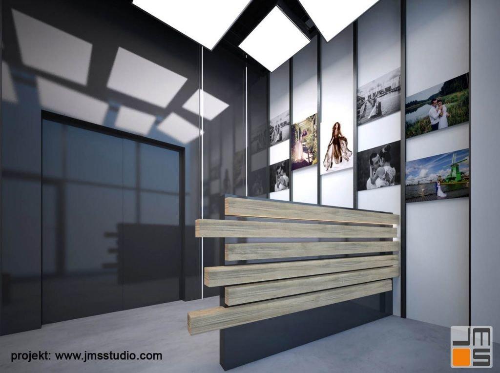 Prace fotograficzne są wyeksponowane na ścianie za ladą do obsługi klienta. Ruszt