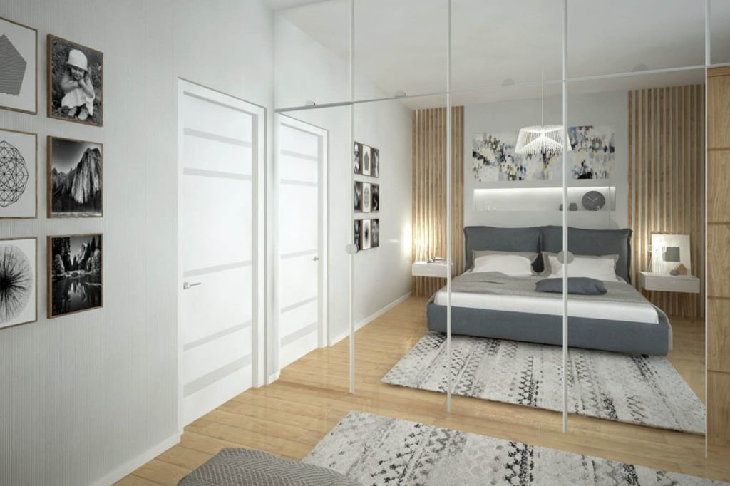 Jasna sypialnia w bieli i szarościach z dużą szafą na garderobę.