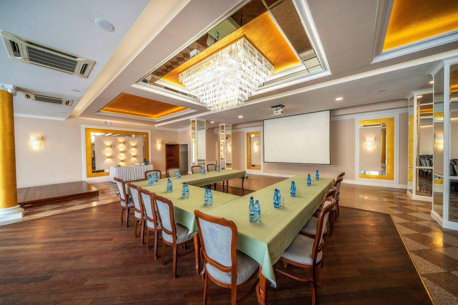 Piękny i efektowny sufit  z lustrami, złotą farbą i wielkim żyrandolem kryształowym to projekt wnętrz eleganckiej sali balowej weselnej w Dworku Skawińskim