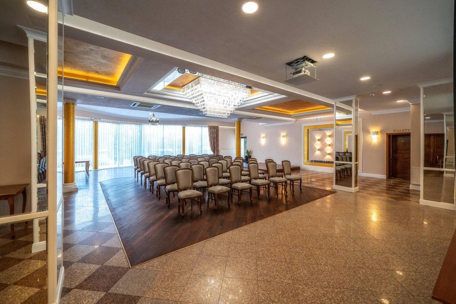 Układ konferencyjny eleganckiej sali weselnej z lustrami i złoty kolor na suficie to projekt wnętrz w Dworku Skawińskim koło Krakowa