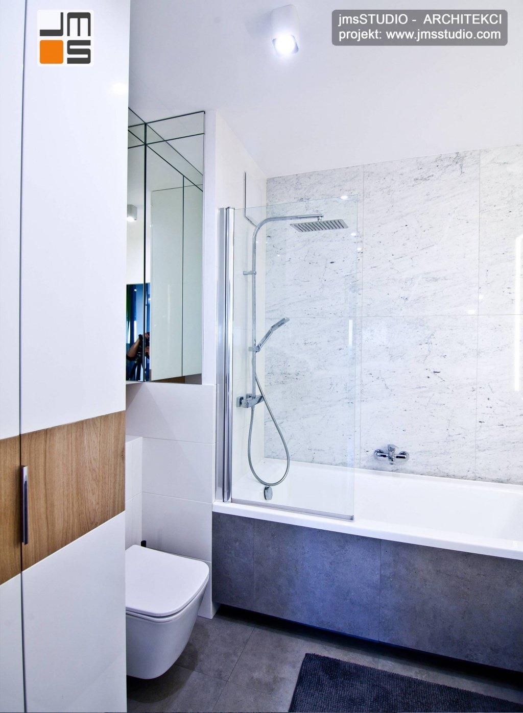 w łazience w bloku z ukrytą pralką w zabudowie zastosowano lustra i marmur
