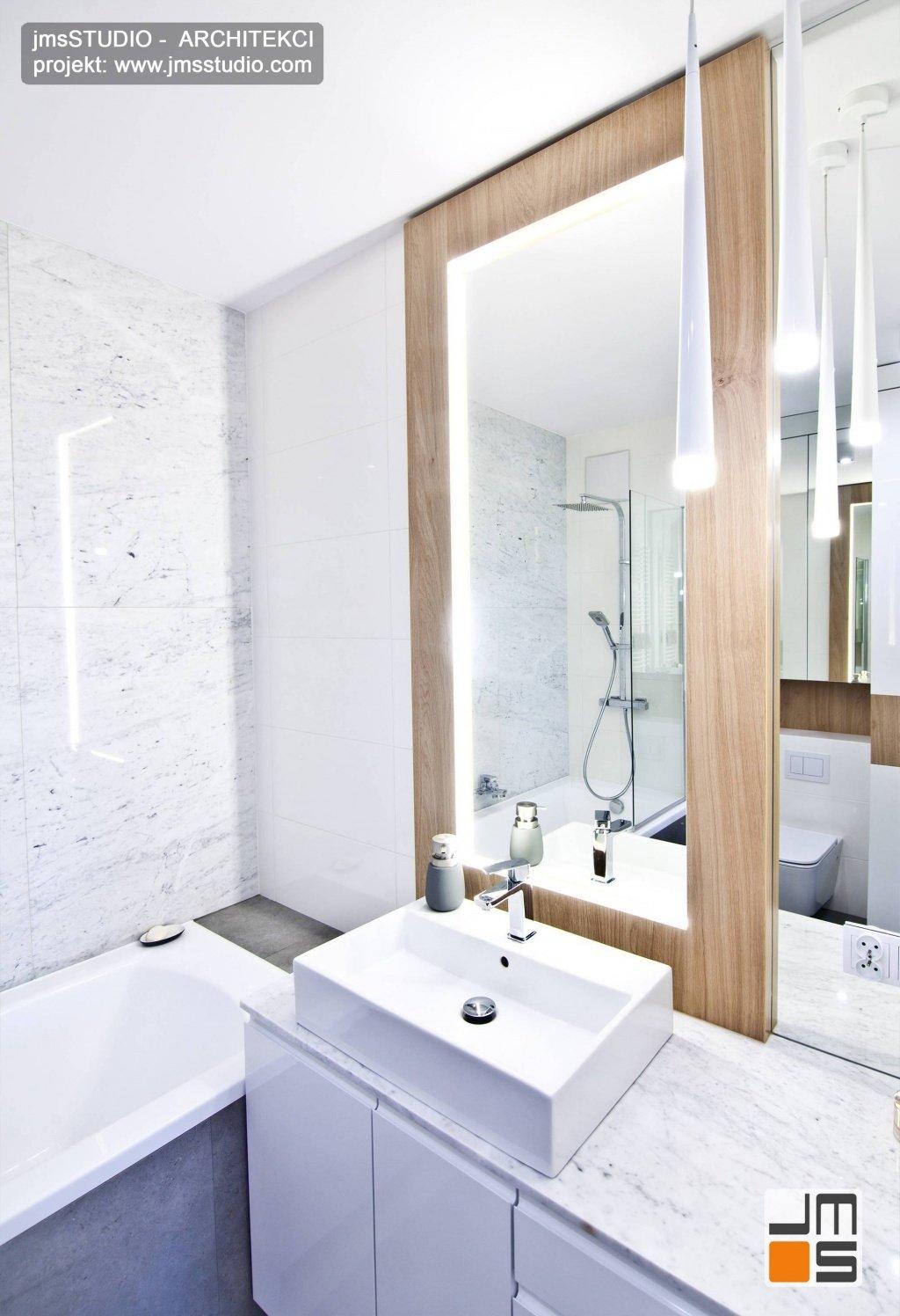 duże lustro w łazience w drewniana rama to elegancki pomysł na dekorację małej łazienki w bloku