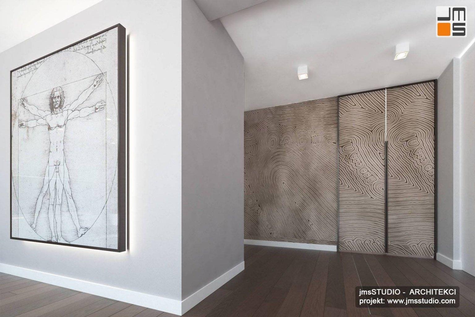 Duża zabudowana szafa wnękowa na wymiar i grafika Leonadro Da Vinci  to projekt aranżacji wnętrz apartamentu w Krakowie