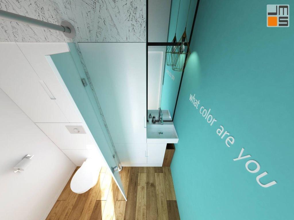 Turkusowo morski kolor ściany z napisem dobrze pasuje do drewnianej podłogi tworząc ciekawy projekt wnętrza małej łazienki w salonie kosmetycznym
