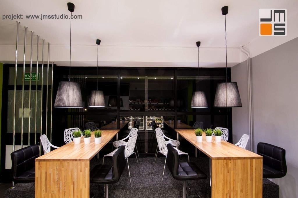 Symetryczny układ mebli w projekcie wnętrz kawiarni tworzy ciekawy efekt we wnętrzu zwłaszcza gdy dochodzi do odbić lustrzanych w szkle witryny