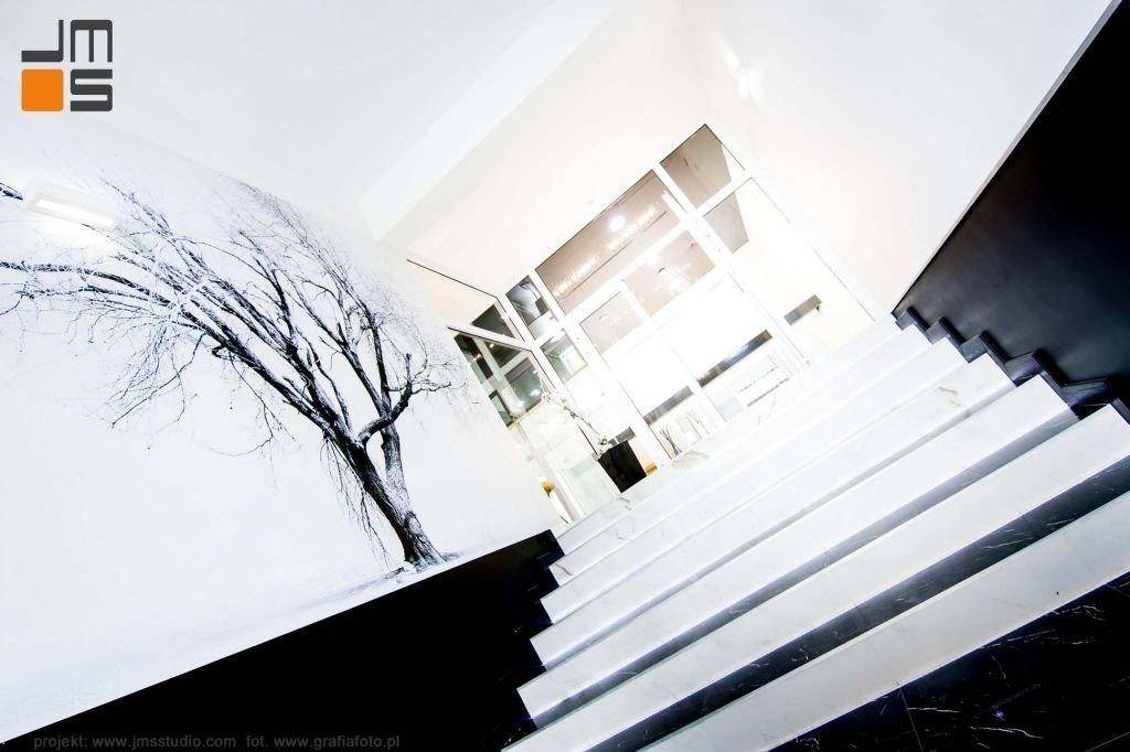 schody okładzina z marmuru czarnego i białe akcenty oraz czarnobiała grafika drzewo we wnętrzu