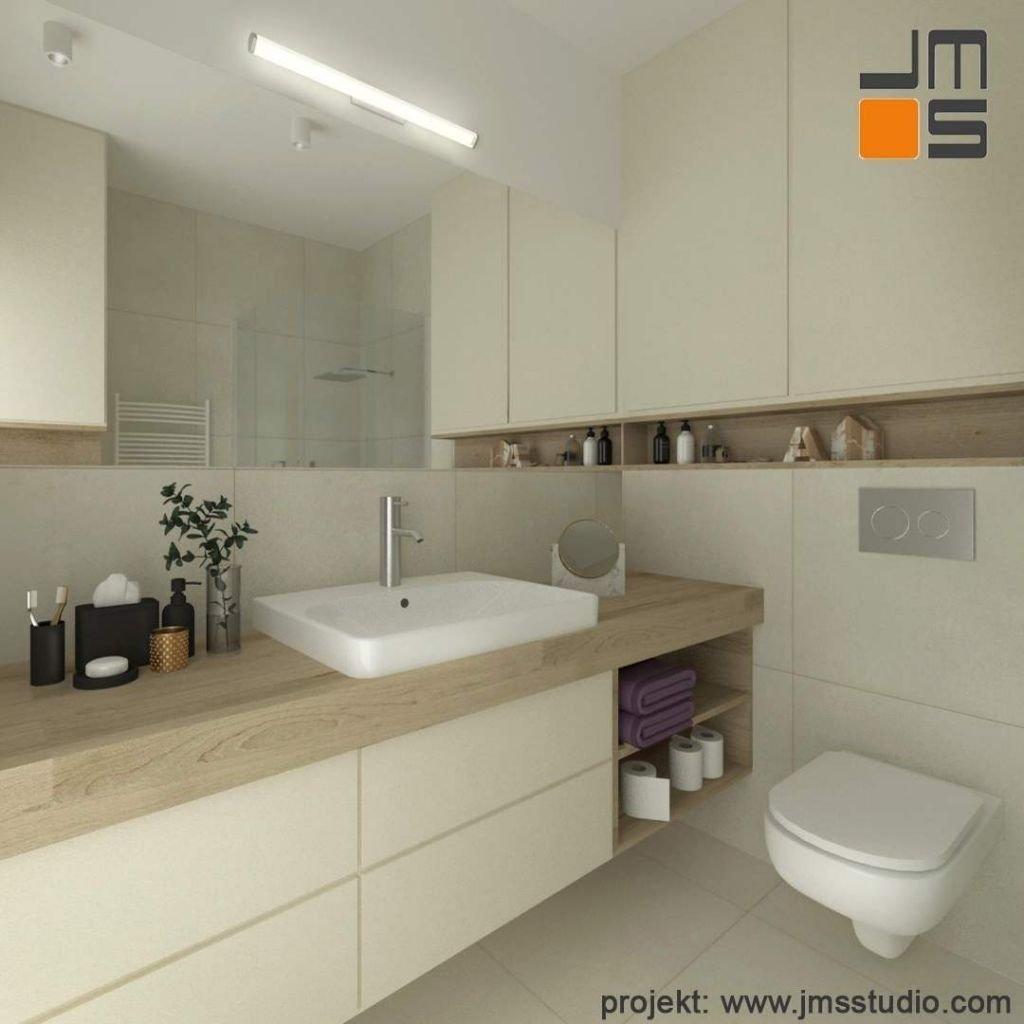 Mała łazienka z armaturą Intuition Bathrooms i ciekawymi meblami z lakierowanymi frontami i drewnem naturalnym