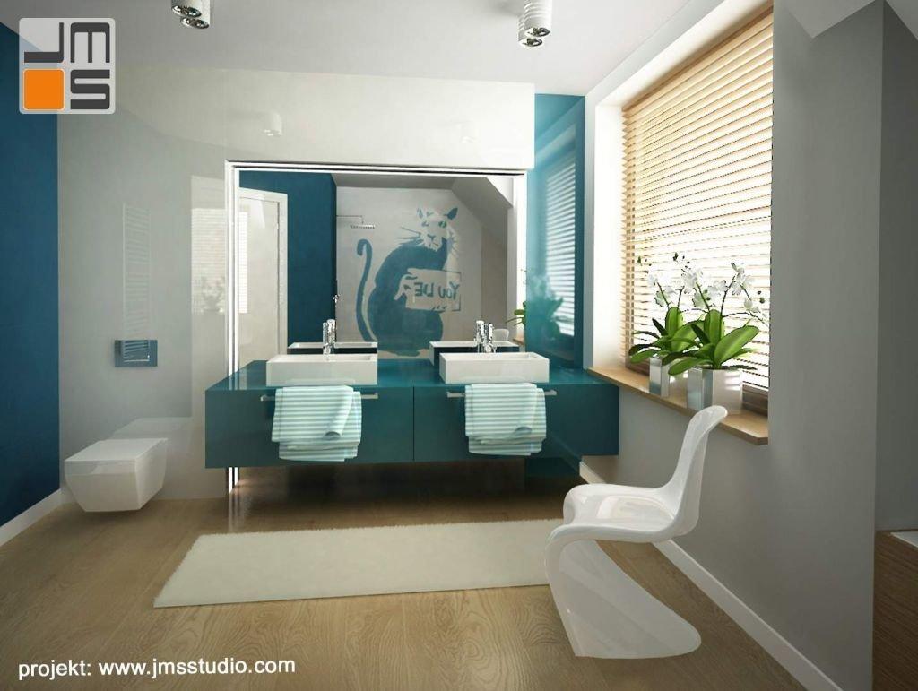 Grafika Banksy jest głównym elementem dekoracyjnym w projekcie nowoczesnej łazienki młodzieżowej w kolorach odcieni niebieskiego