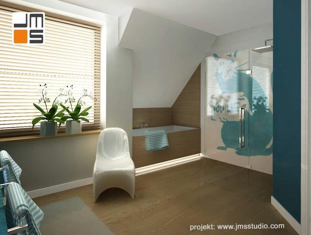 Wanna w zabudowie fornirowanej oraz szkalna kabina prysznicowa stanowia tło dla grafiki Banksy w projekcie nowoczesnej łzaienki na poddaszu