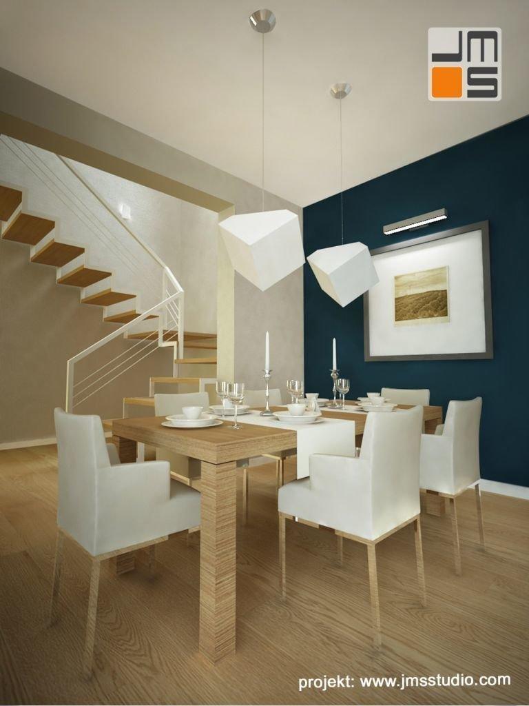 Projekt wnętrz jadalni z grafiką i turkusową ścianą oraz dużym stołem