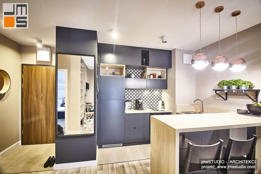 Ciemne meble kuchenne i duże lustro tworzą mocny akcent kolorystyczny w projekcie wnętrz mieszkania w stylu soft-loft w Krakowie. Durze lustro powoduje optyczne powiększenie przestrzeni