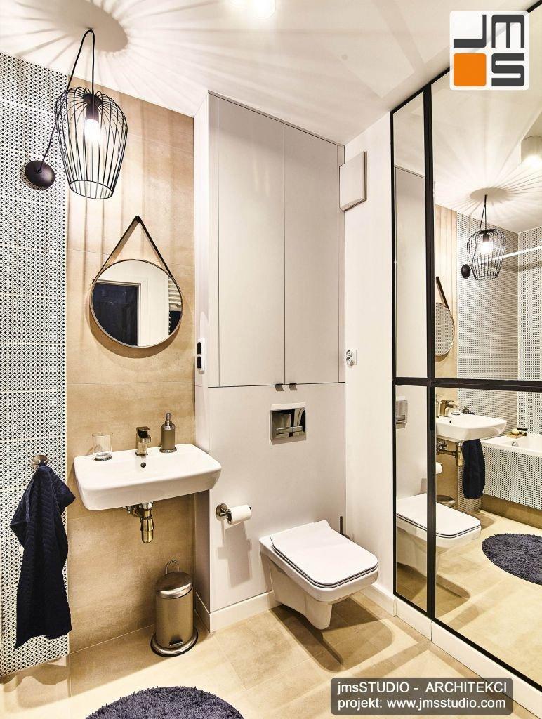 SOFT LOFT czyli projekt wnętrz łazienki z białymi meblami i płytkami z czarnymi dodatkami jak designerska lampa czy lustro oraz gresem w ciepłym beżowym kolorze