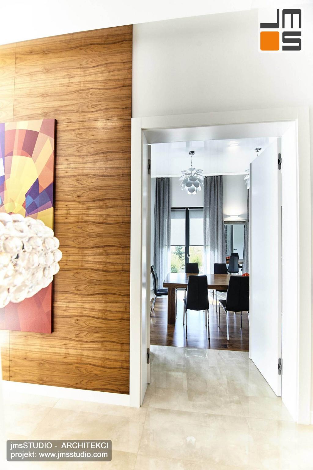 2018 06 z przestrzeni salonu z ciekawą grafiką na ścianie można przejść do elegancko zaprojektowanego wnętrza jadalni z dużym stołem i ciekawymi lampami