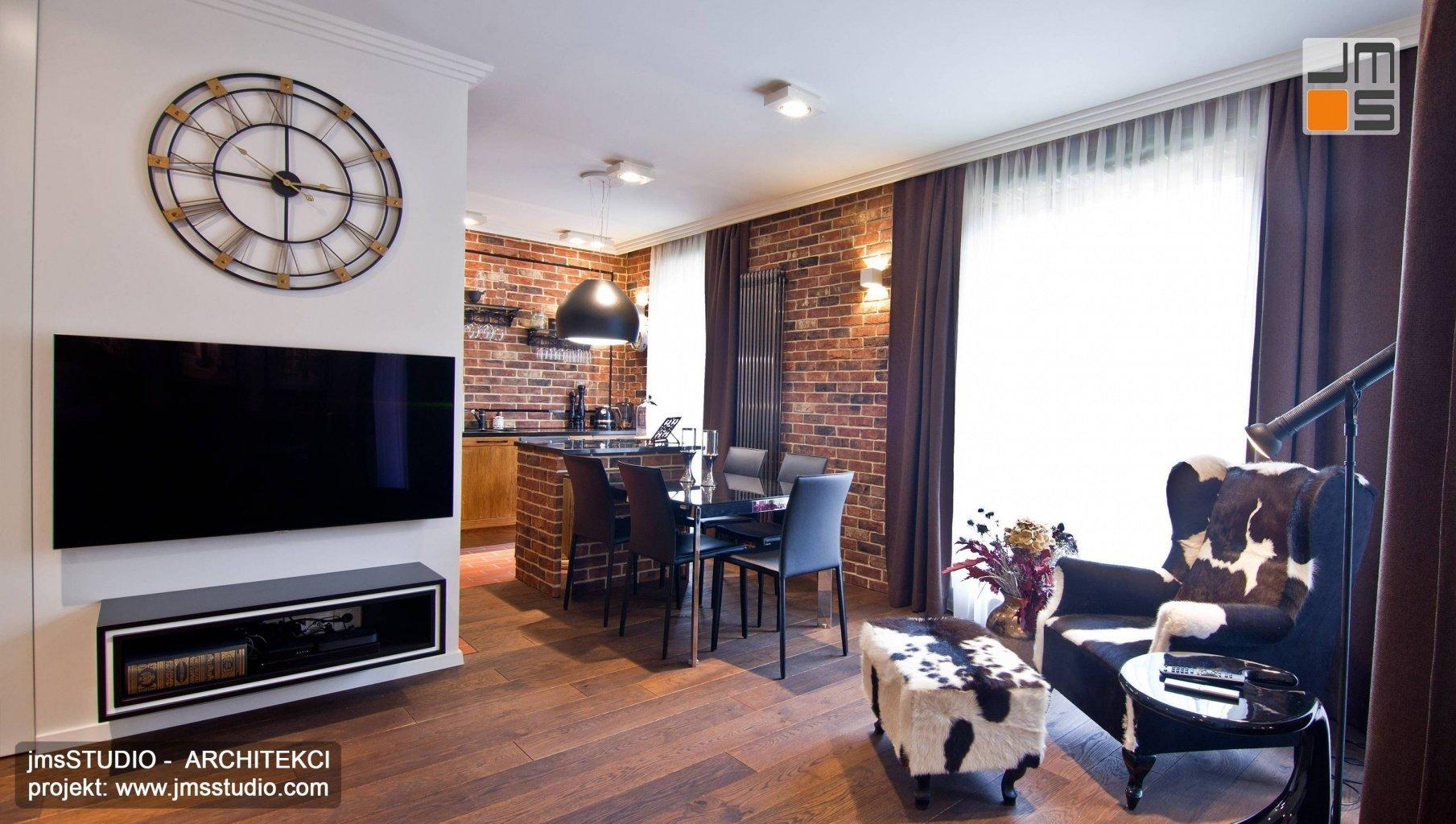 Projekt wnętrz rustykalnych z dużym zegarem w salonie i cegłą na ścianie w kuchni i jadalni