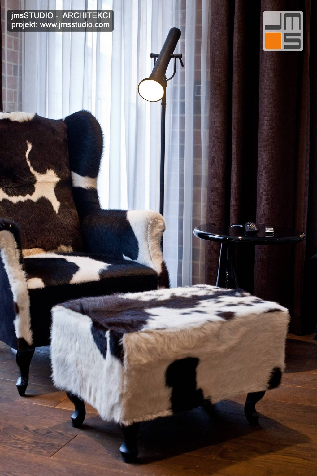 Projekt wnętrz kącika do czytania to designerski fotel i pufa skórzana oraz podłoga dąb wędzony olejowana dla eleganckie wnętrze rustykalne