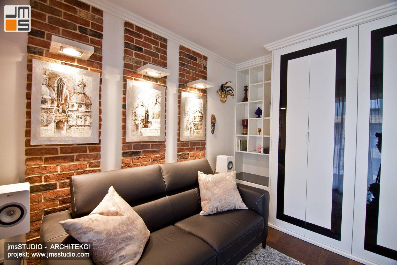 Projekt wnętrz z dużą zabudowaną szafą z lakierowanymi frontami i pomysł na ścianę z cegły w mieszkaniu w Krakowie