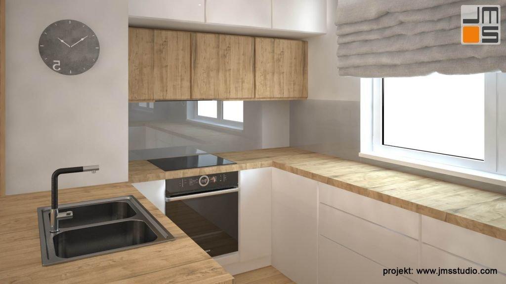 Białe fronty kuchenne z uchwytami frezowanymi w zestawieniu z drewnianym blatem i ciemnymi sprzętami.