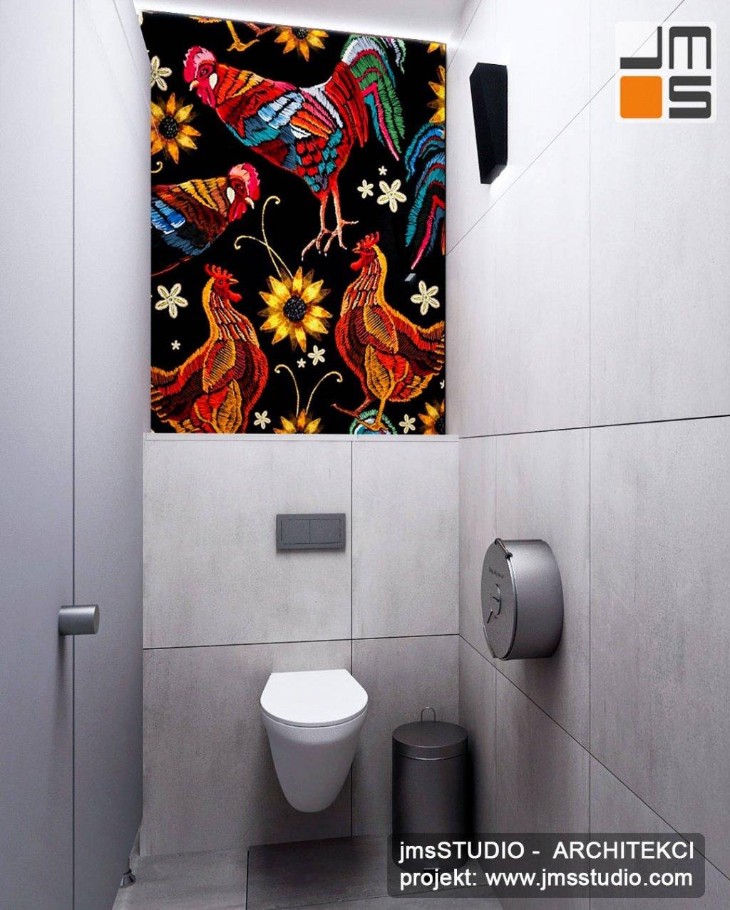 Ciekawy pomysł na łazienkę toaletę w restauracji z  szarymi płytkami u kolorowa grafika na szkle na scianie