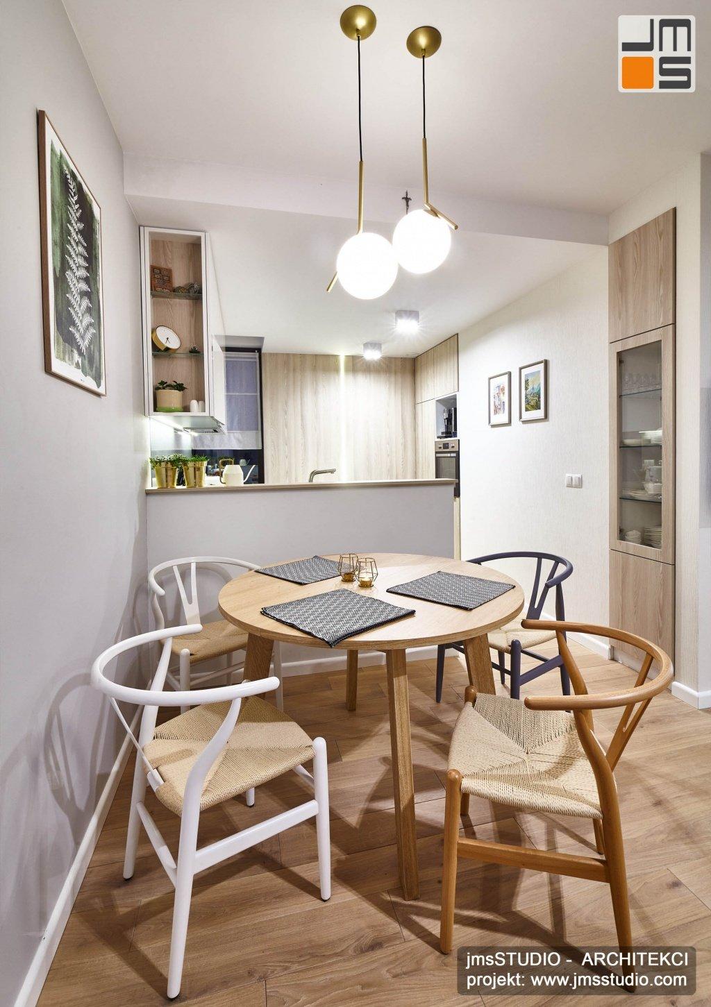 Pomysł na prosty projekt wnętrz nowoczesnej małej jadalni w stylu skandynawskim z eleganckimi lampami