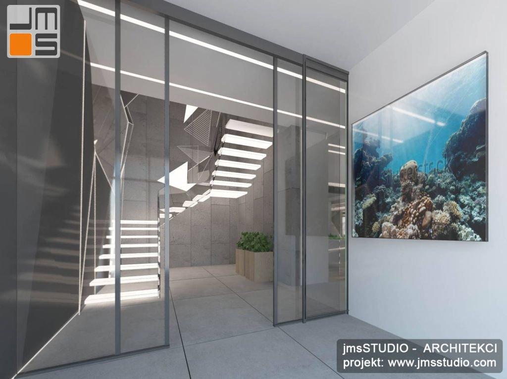 projekt wnętrz holu wejściowego do nowoczesnego domu jednorodzinnego z akwarium morskim i betonem architektonicznym we wnętrzu