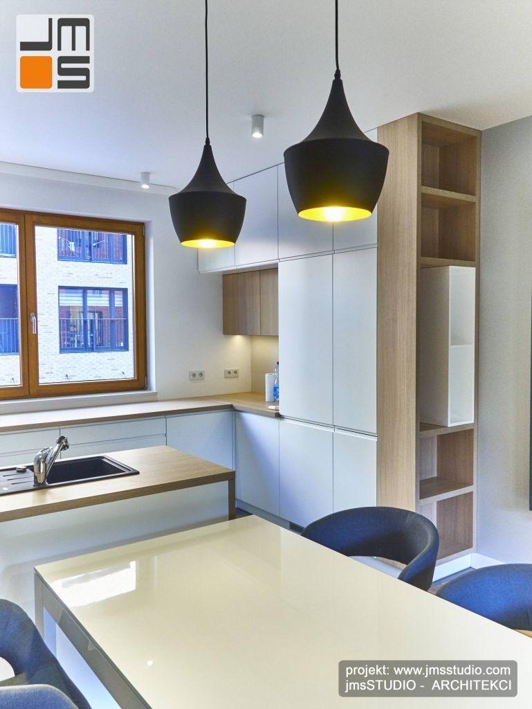 Designerskie czarno złote lampy wiszące daja dobre oświetlenie nad stołem w jadalni małego mieszkania w Kakowie