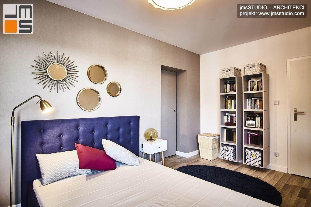 W projekcie wnętrz tej ciekawej sypialni w stylu SOFT LOFT zastosowano ciekawą dekorację ściany wykończonej tapetą, polegającą na powieszeniu na niej luster w różnych ramach